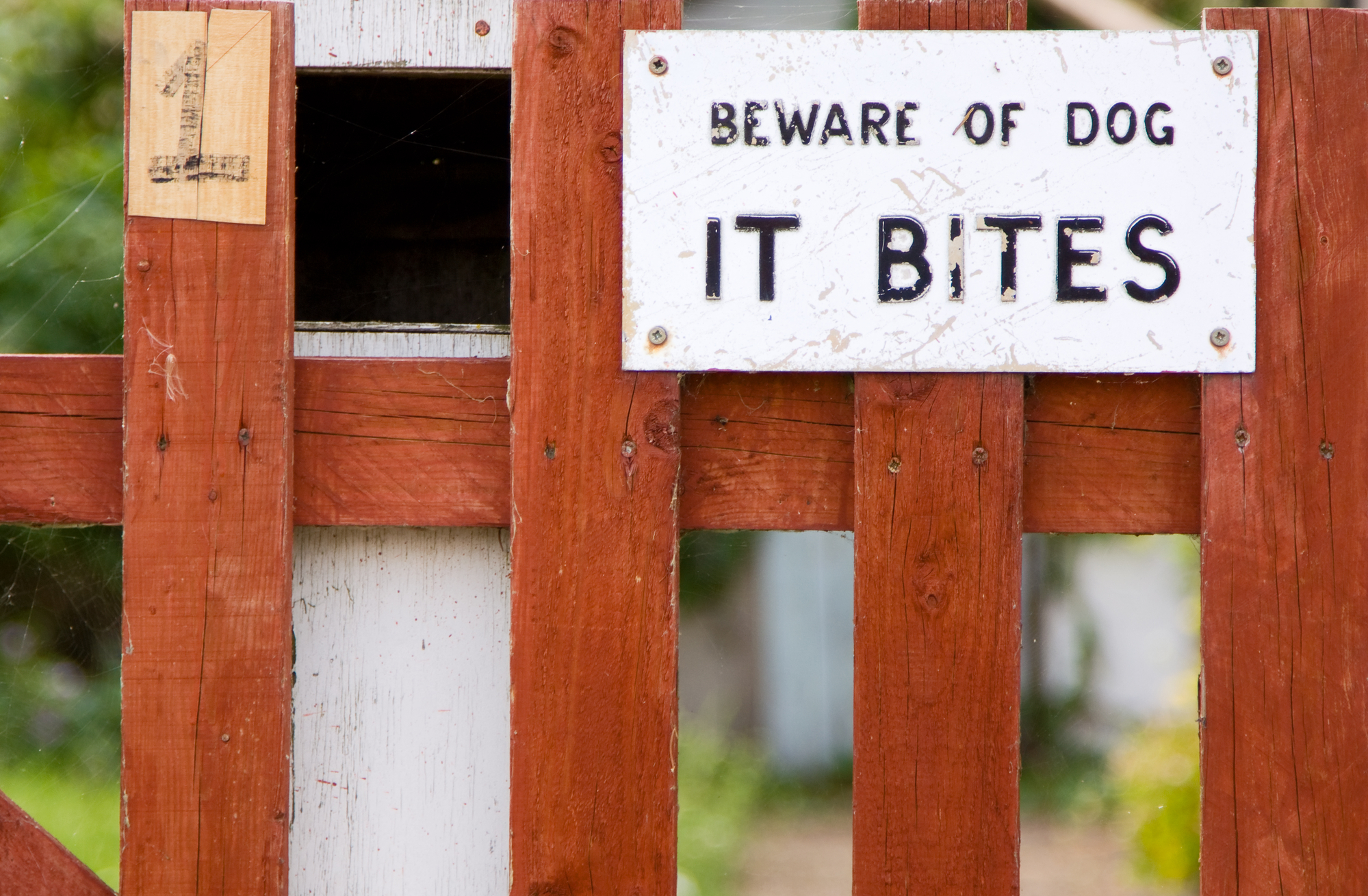 """Setting boundaries image shows fence with a sign that reads """"Beware of dog. It bites."""""""